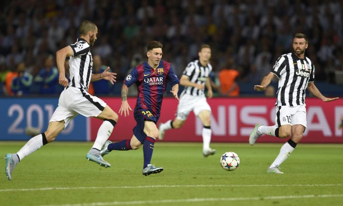 Barcelona's Argentinian forward Lionel Messi (in dark uniform) runs with the ball during the UEFA Champions League final football match between Juventus and FC Barcelona at the Olympic Stadium in Berlin on Saturday. (LLUIS GENE/AFP/Getty Images)