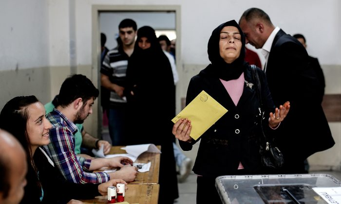 A Turkish woman reacts before casting her vote for Turkey's legislative election at a polling station in Istanbul on June 7, 2015. (YASIN AKGUL/AFP/Getty Images)