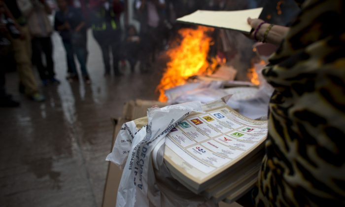 A group of citizens, led by parents of missing students from Ayotzinapa, burn election materials in Tixtla, Guerrero State, Mexico, Sunday, June 7, 2015. The group burned all materials from several polling stations, before meeting resistance from another group of town residents. (AP Photo/Rebecca Blackwell)