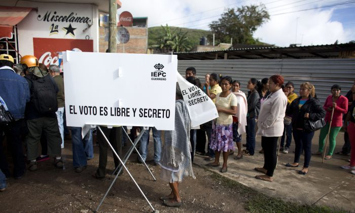 "A town resident completes her election ballot, behind a screen reading in Spanish ""Voting is free and secret,"" at a polling station defended by scores of residents, in Tixtla, Guerrero State, Mexico, Sunday, June 7, 2015. (AP Photo/Rebecca Blackwell)"