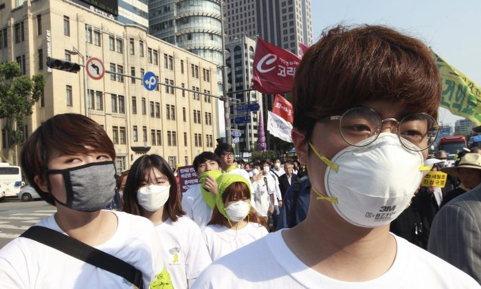 Protesters wear masks as a precaution against the MERS, Middle East Respiratory Syndrome, virus as they march after a rally against government's labor policy in Seoul, South Korea, Sunday, June 7, 2015. (AP Photo/Ahn Young-joon)