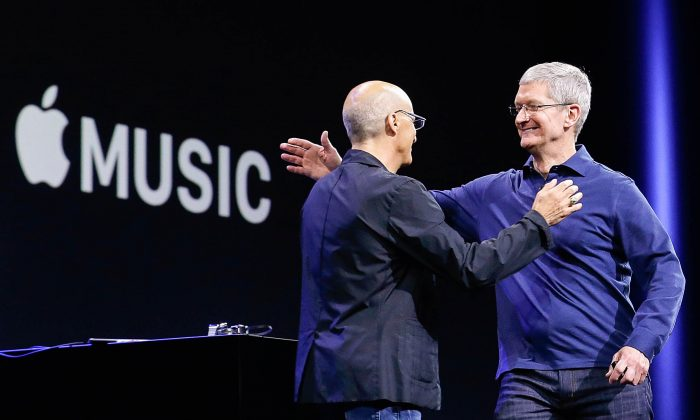 Apple CEO Tim Cook, right, hugs Beats by Dre co-founder and Apple employee Jimmy Iovine at the Apple Worldwide Developers Conference in San Francisco, Monday, June 8, 2015. (AP Photo/Jeff Chiu)