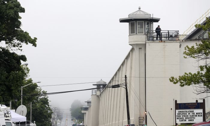 A guard stands on the wall at Clinton Correctional Facility on Monday, June 8, 2015, in Dannemora, N.Y. Two murderers who escaped from the prison by cutting through steel walls and pipes remain on the loose Monday as authorities investigate how the inmates obtained the power tools used in the breakout. (AP Photo/Mike Groll)