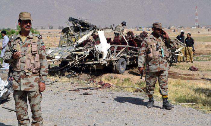 Pakistani security officials keep watch near a destroyed vehicle used by security forces following a bomb attack on the outskirts of Quetta, the capital of restive Baluchistan province, on May 23, 2013. (Banaras Khan/AFP/Getty Images)
