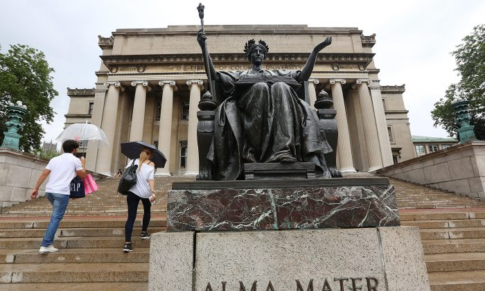 People walk past the Alma Mater statue on the Columbia University campus in New York on July 1, 2013. (Mario Tama/Getty Images)