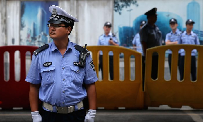 Chinese policemen guard outside the Jinan Intermediate People's Court, on August 25, 2013 in Jinan, China. (Feng Li/Getty Images)