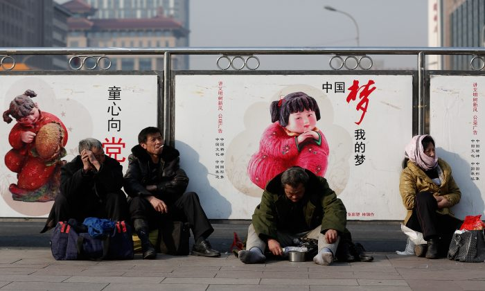 A beggar sits front government propaganda at Beijing Railway Station on March 2, 2014 in Beijing, China. Developed economies are based on a broad middle class—precisely what has not been attained in China. (Lintao Zhang/Getty Images)