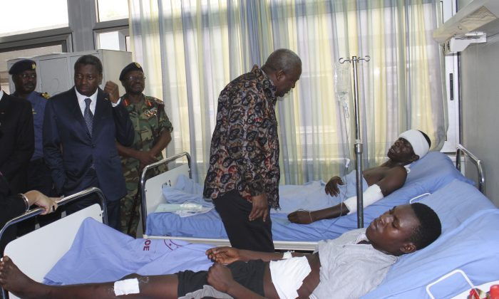 Ghana President John Dramani Mahama, center, and Togo President Faure Gnassingbe, second left, visit victims of the gas station explosion at the military hospital in Accra, Ghana, Friday, June 5, 2015. (AP Photo)