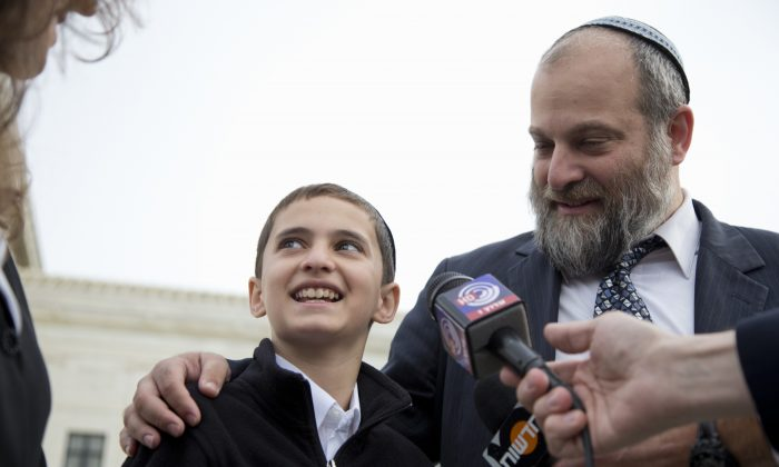 Menachem Zivotofsky and his father Ari Zivotofsky speaks to media outside the Supreme Court in Washington. The Supreme Court has struck down a disputed law that would have allowed Americans born in Jerusalem to list their birthplace as Israel on their U.S. passports.  (AP Photo/Carolyn Kaster)