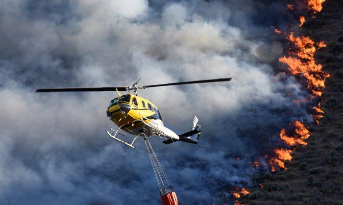 Emergency responders dump water onto a wildfire on June 6, 2015, near Celebration Park south of Melba, Idaho.  (Adam Eschback/The Idaho Press-Tribune via AP)