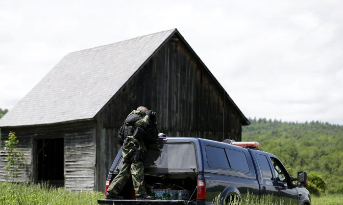 A heavily armed law enforcement officer looks over a field through binoculars during a search for two escaped killers near Boquet, N.Y., Tuesday, June 9, 2015.  State and federal law officers are searching for David Sweat and Richard Matt,  two killers who used power tools to break out of Clinton Correctional Facility in Dannnemora, close to the Canadian border.  (AP Photo/Seth Wenig)