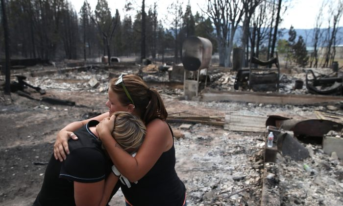 A mother and daughter hold each other as they in the burned-out ruins of what used to be their home Weed, Calif., on Sept. 16, 2014. (Justin Sullivan/Getty Images)