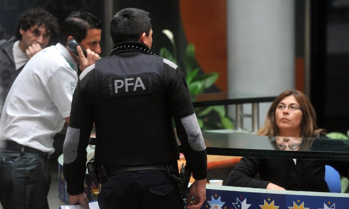 A member of Interpol is seen speaking with staff at the headquarters of Argentine sports broadcaster Torneos y Competencias during a raid in Buenos Aires on May 29, 2015. (STR/AFP/Getty Images)