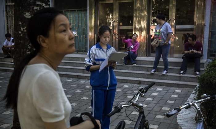 A Chinese student does some last minute studying as her mother looks on outside of the Beijing No. 4 High School, one of the most prestigious in the country, before writing the Gaokao on June 8, 2015 in Beijing, China. (Kevin Frayer/Getty Images