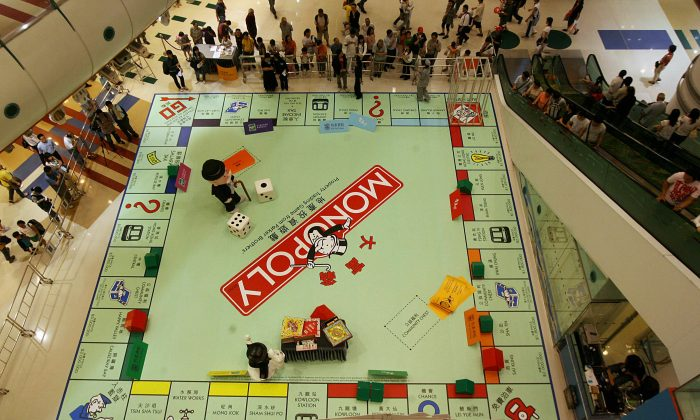 People watch a giant Monopoly board as a game is about to get underway in Hong Kong on Oct. 26, 2006. Since Monopoly was first sold commercially in the 1930s, it has become a part of popular world culture, locally licensed in more than 100 countries and printed in 37 languages. (Mike Clarke/AFP/Getty Images)