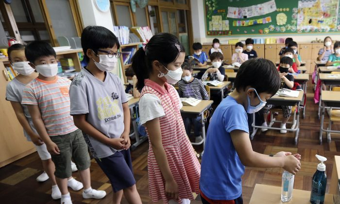 South Korean elementary school students wear masks as a precaution against the MERS, Middle East Respiratory Syndrome, virus as they sanitize their hands to protect against possible MERS virus at an elementary school in Busan, South Korea, Tuesday, June 9, 2015. South Korea is determined to end this week the outbreak of Middle East Respiratory Syndrome, saying upcoming several days will be a critical moment on whether to overcome the medical crisis.(Cha Geun-ho/Yonhap via AP)