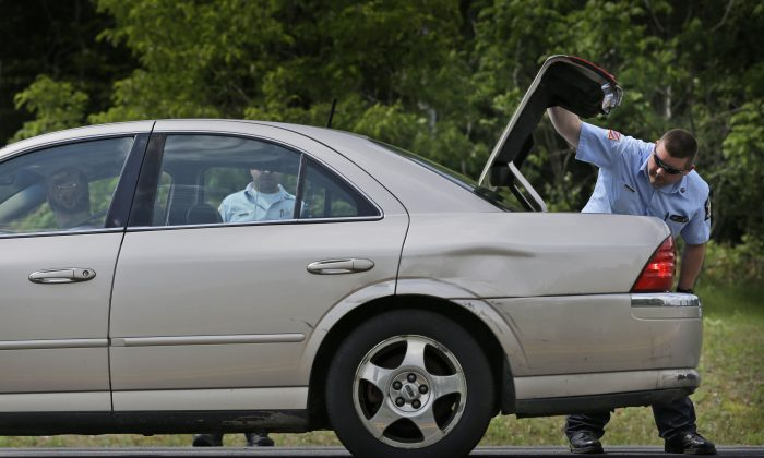 Law enforcement officials check the trunk of a car at a check point near the border of Dannemora, N.Y., Wednesday, June 10, 2015. Police were resuming house-to-house searches near the maximum-security prison in northern New York where David Sweat and Richard Matt , two killers escaped using power tools.  (AP Photo/Seth Wenig)