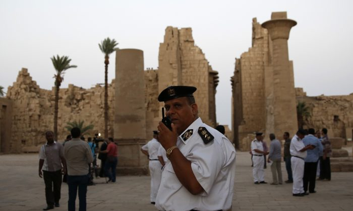 Egyptian security officials stand guard as tourists visit the ruins of the Karnak Temple in Luxor, Egypt, Wednesday, June 10, 2015. (AP Photo/Hassan Ammar)