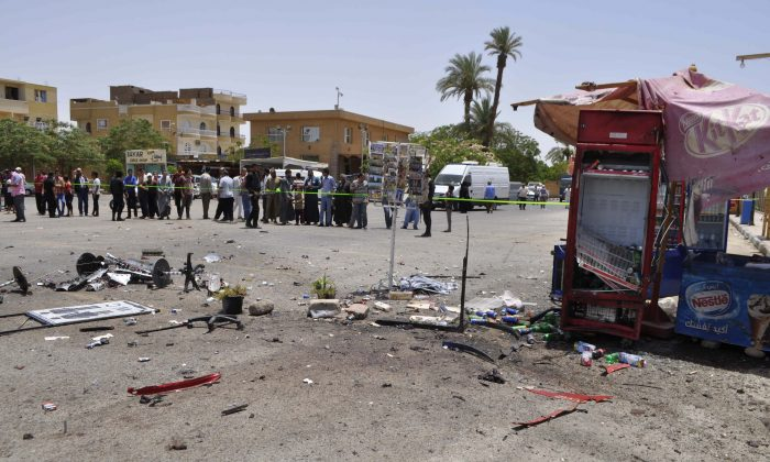 A crowd looks on at the site of a suicide bombing, near Karnak Temple in Luxor, Egypt, Wednesday, June 10, 2015. (AP Photo)
