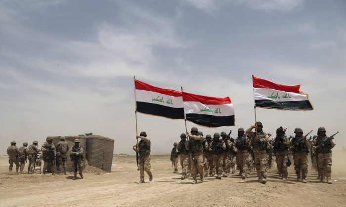 U.S. soldiers (L) participate in a training mission with Iraqi army soldiers outside Baghdad, Iraq, on May 27, 2015. (AP Photo/Khalid Mohammed)