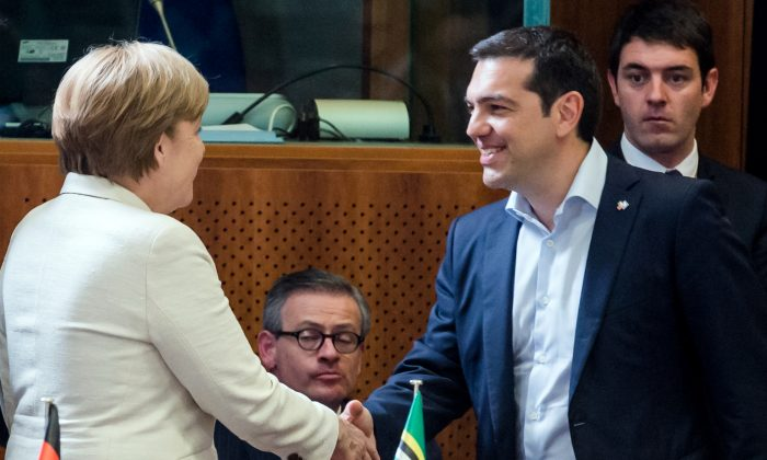 Greek Prime Minister Alexis Tsipras, right, shakes hands with German Chancellor Angela Merkel during a round table meeting at the EU-CELAC summit in Brussels on Wednesday, June 10, 2015. (AP Photo/Geert Vanden Wijngaert)
