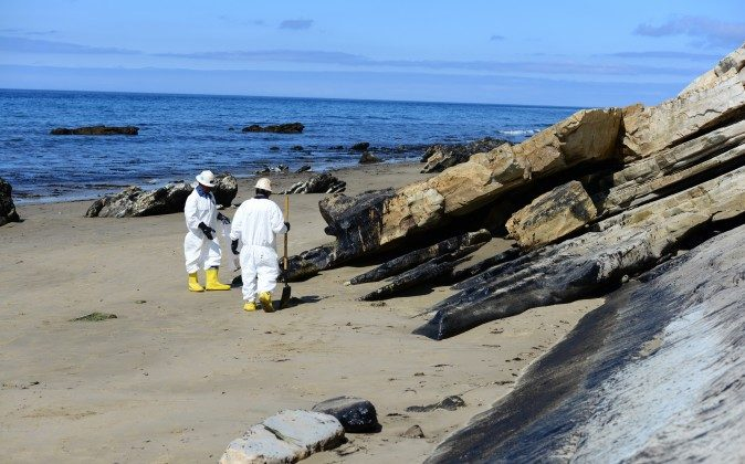 In this Saturday, May 23, 2015 photo released by the U.S. Coast Guard, two cleanup crew members work to remove oil from the sand along a portion of soiled coastline near Refugio State Beach, north of Goleta, Calif. (Chief Petty Officer David Mosley/U.S. Coast Guard via AP)