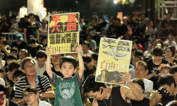 "A boy holds a banner reading ""Vindicate the June 4 Movement, We Demand Democracy and True Universal Suffrage"" on June 4, 2015. (Epoch Times)"