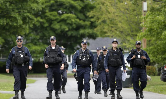Law enforcement officers walk the streets in Dannemora, N.Y., as they searched houses near the maximum-security prison in northern New York where two killers escaped using power tools, Wednesday, June 10, 2015. (AP Photo/Seth Wenig)