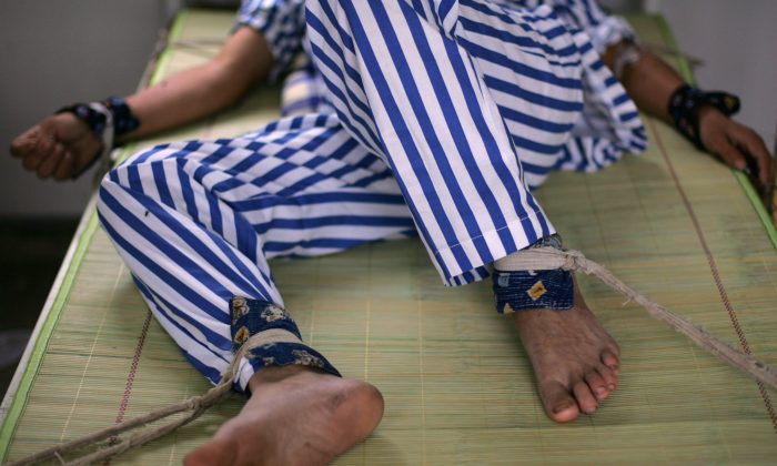 A mental patient lies in bed with arms and legs being bound at the Anxian Mental Hospital in Anxian County of Sichuan Province, China on Aug. 24, 2008. (China Photos/Getty Images)