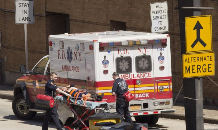 An injured person is carried on a stretcher to an ambulance at the entrance to the Lincoln Tunnel, Wednesday, June 10, 2015 in New York.  (AP Photo/Mark Lennihan)