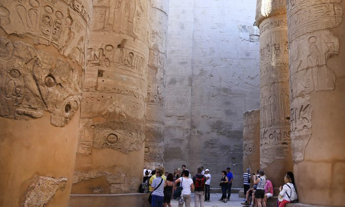FILE - In this Sunday, Nov. 30, 2014, file photo, tourists point out the hieroglyphic on columns in the Hypostyle Hall at the Karnak Temple in Luxor, Egypt. (AP Photo/Hassan Ammar, File)