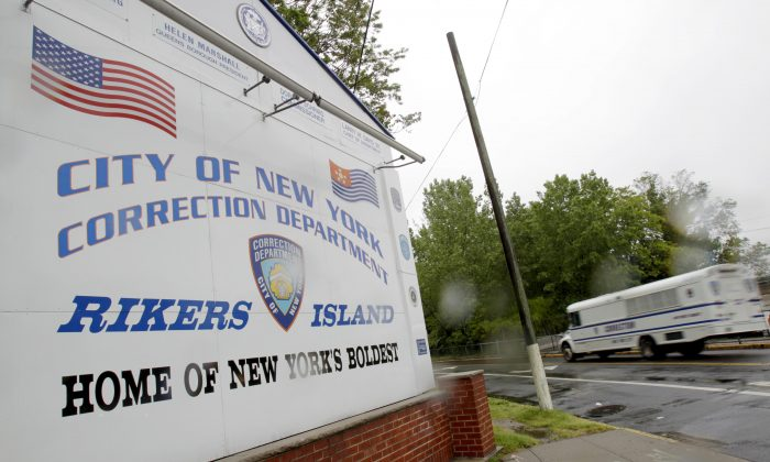 A bus drives past the the entrance to Rikers Island in New York. Overall performance of the private health care provider for New York City's jails failed to improve last year amid heightened scrutiny over inmate deaths that put the company's contract under review, according to an evaluation obtained by The Associated Press. (AP/Seth Wenig)