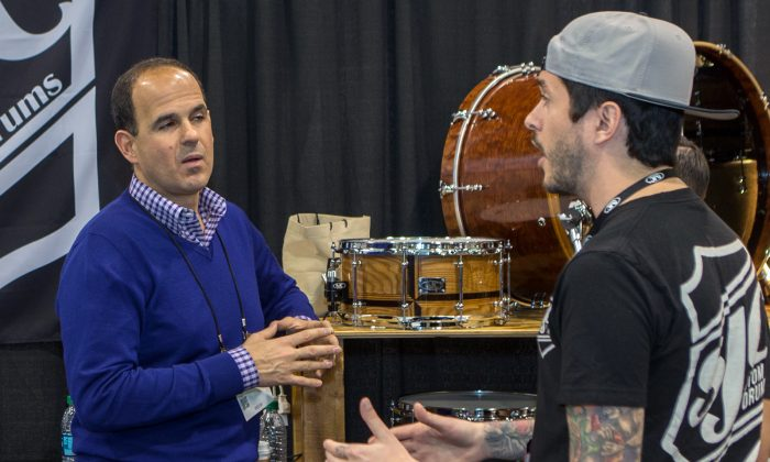 """In this Jan. 24, 2015, photo, Marcus Lemonis, of the TV show """"The Profit,"""" left, films at the SJC Custom Drums booth during the 2015 National Association of Music Merchants (NAMM) show at the Anaheim Convention Center in Anaheim, Calif. (Photo by Paul A. Hebert/Invision/AP)"""