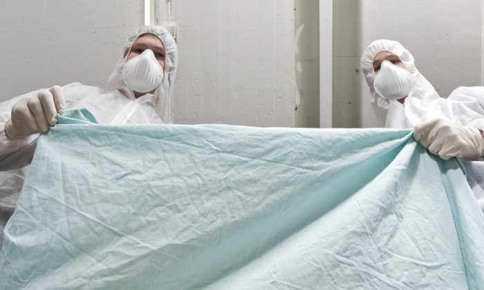 A file photo of forensic investigators covering a dead victim. (36clicks/iStock)