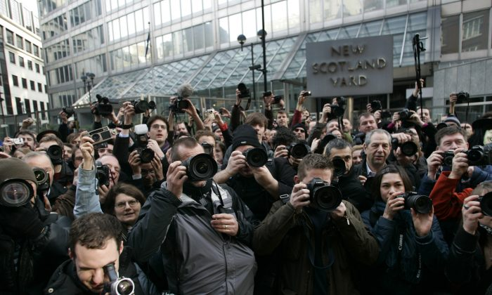 Photographers take pictures outside British police headquarters to protest against new anti-terror legislation that they claim could hamper journalists from taking pictures at public demonstrations, in central London, Monday, Feb. 16, 2009. Photographers say part of the new counterterrorism measure will give police the right to stop anyone taking pictures of police officers or the armed services. The measure takes effect Monday. (AP Photo/Lefteris Pitarakis)