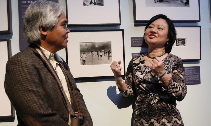 """The Associated Press photographer Huynh Cong """"Nick"""" Ut, left, and Kim Phuc Phan Thi, UNESCO Goodwill Ambassador visit the photo exhibit """"War/Photography: Images of Armed Conflict and Its Aftermath"""" on display at Annenberg Space for Photography in Los Angeles, Saturday, May 11, 2013. The show runs run through June 2. Ut's iconic black-and-white image of Phuc, seen between them, after a napalm attack in 1972 communicated the horrors of the Vietnam War. (AP Photo/Damian Dovarganes)"""