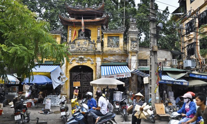 Typical scene in Hanoi, motor-cycles (scooters), and shops that expose on the road the items for sale. (iStock)