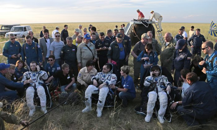 The International Space Station (ISS) crew rest after their landing, in the Russian Soyuz TMA-15M space capsule seen behind, with Russian cosmonaut Anton Shkaplerov, centre, U.S. astronaut Terry Virts, left, and Italian astronaut Samantha Cristoforetti, in remote area outside the town of Dzhezkazgan, Kazakhstan, on Thursday, June 11, 2015. (AP Photo/Ivan Sekretarev)