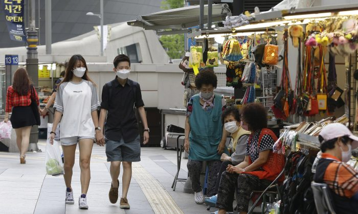 A couple wears masks as a precaution against Middle East Respiratory Syndrome (MERS) as they pass by street vendors wait for customers at Dongdaemoon market in Seoul, South Korea, Thursday, June 11, 2015. (AP Photo/Ahn Young-joon)