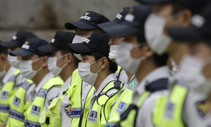 South Korean police officers wearing masks as a precaution against Middle East Respiratory Syndrome (MERS) stand guard during a rally in Seoul, South Korea, Thursday, June 11, 2015. (AP Photo/Lee Jin-man)