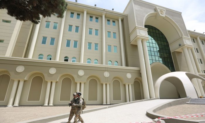 "U.S. military personnel walk near Afghanistan's new Defense Ministry building, in Kabul, Afghanistan on May 6, 2015. In Kabul, they call it the ""mini Pentagon,"" the new headquarters for Afghanistan's Ministry of Defense. (AP Photo/Rahmat Gul)"