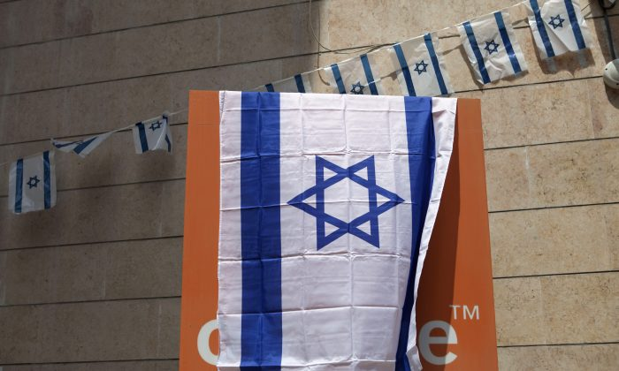 "The Orange company logo is seen covered with an Israeli flag at the ""Partner Orange"" Communications Company's offices in the city of  Rosh Haain, Israel, Thursday, June 4, 2015. (AP Photo/Dan Balilty)"