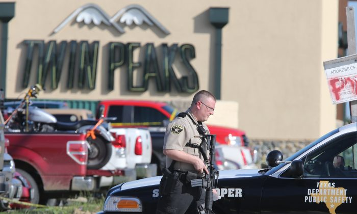 In this May 17, 2015 file photo, authorities investigate a shooting in the parking lot of the Twin Peaks restaurant, in Waco, Texas. (AP Photo/Jerry Larson, File)