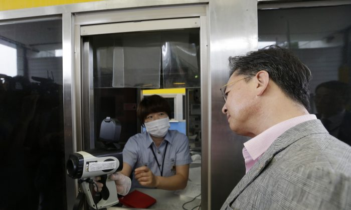 South Korean Unification Minister Hong Yong-pyo, right, watches a thermal camera monitor after checking his body temperature as a precaution against Middle East Respiratory Syndrome (MERS) virus at the customs, immigration and quarantine gate in Paju, South Korea, near the border village of Panmunjom, South Korea, Saturday, June 13, 2015. Experts from the World Health Organization and South Korea on Saturday downplayed concerns about the MERS virus spreading further within the country, but said that it was premature to declare the outbreak over.(AP Photo/Ahn Young-joon)