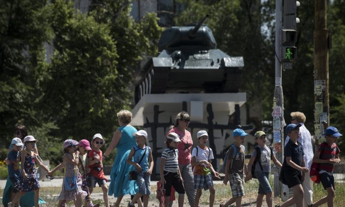 In this photo taken on Thursday, June  11, 2015, children cross the road in front of a memorial of the WWII in the town of Severodonetsk, Luhansk region, eastern Ukraine.  Pro-Russian sympathies have historically been strong here, in a region where Ukrainian identity has tended to be much weaker than elsewhere in the country.  (AP Photo/Evgeniy Maloletka)