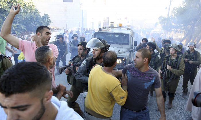 Palestinian scuffle with Israeli soldiers after a Palestinian was killed in clashes with Israeli forces in the village Kafr Malik near the West Bank city of Ramallah, Sunday, June 14, 2015. (AP Photo/Majdi Mohammed)