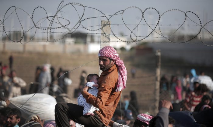 A Syrian refugee carries a baby over the broken border fence into Turkey after breaking the border fence and crossing from Syria in Akcakale, Sanliurfa province, southeastern Turkey, on Sunday. (AP Photo/Lefteris Pitarakis)