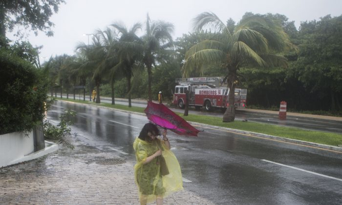 A woman has her umbrella twisted by the strong winds of a tropical storm as she walks down the main hotel strip in Cancun, Mexico, Sunday, June 14, 2015. (AP Photo/Christian Palma)