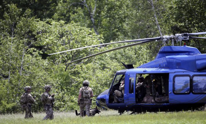 Law enforcement officers walk to a waiting helicopter after searching a wooded area near the Saranac River on Sunday, June 14, 2015, in Saranac, N.Y. (AP Photo/Mike Groll)