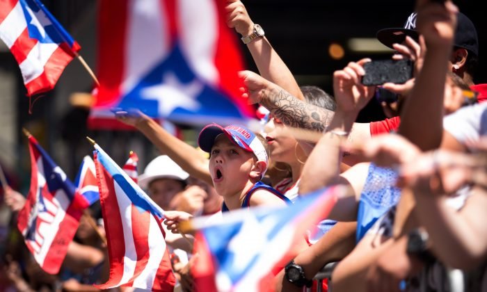 Jaydden Garcia (C), 8, cheers as the annual National Puerto Rican Day Parade makes its way up New York's Fifth Ave., Sunday, June 14, 2015.  (AP Photo/Kevin Hagen)